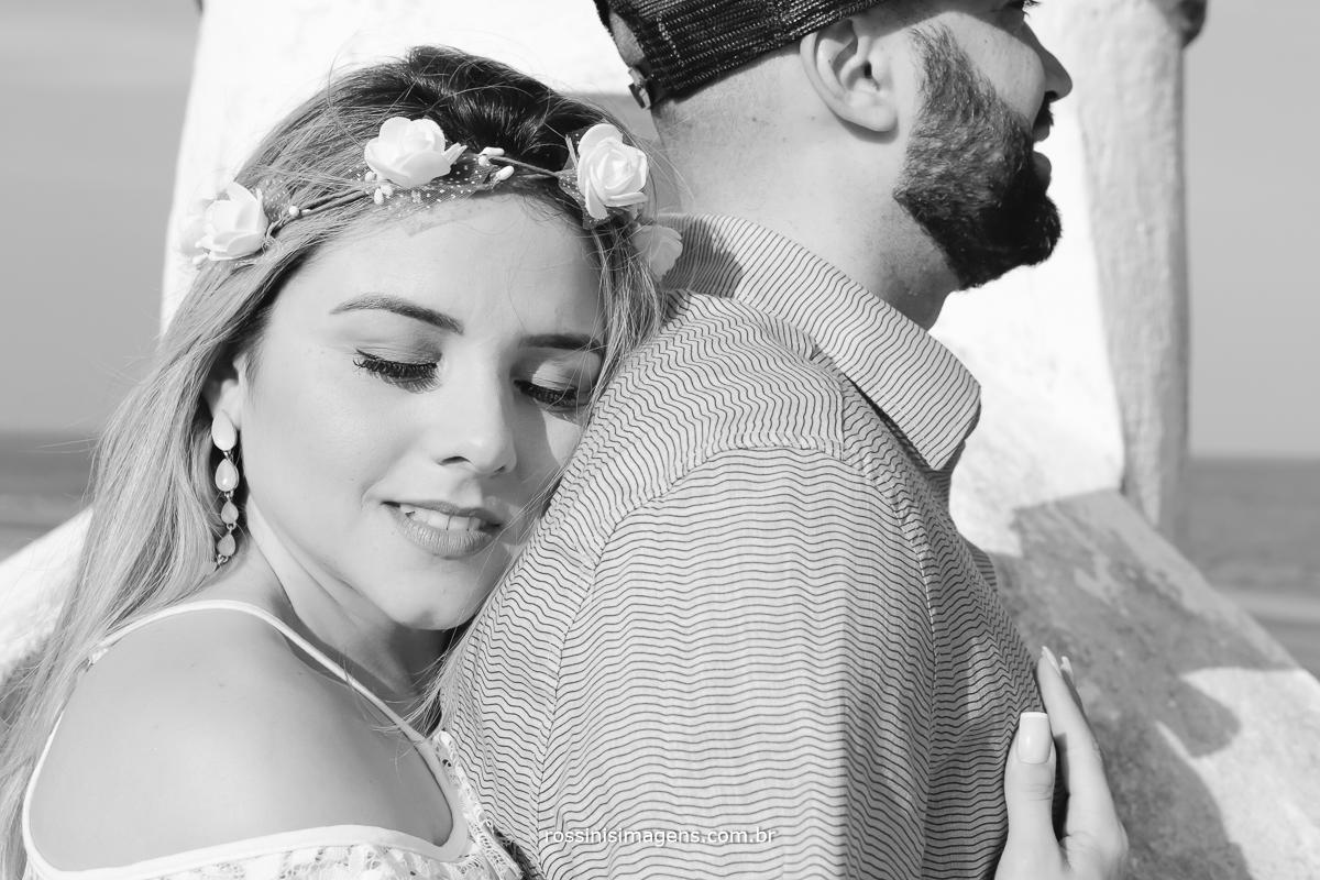 noiva aconchegada no noivo em ensaio na praia para o casamento