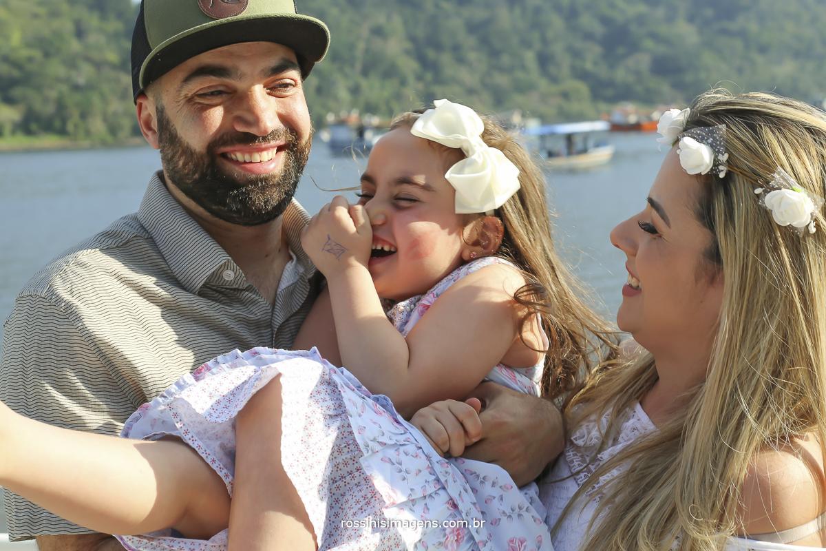 casal sorrindo com a filha no colo em ensaio fotográfico na praia