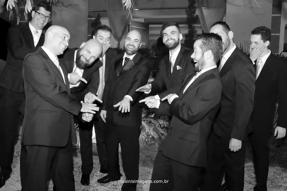 Padrinho brincando com noivo por ele ter casado mostrando a aliança de ouro