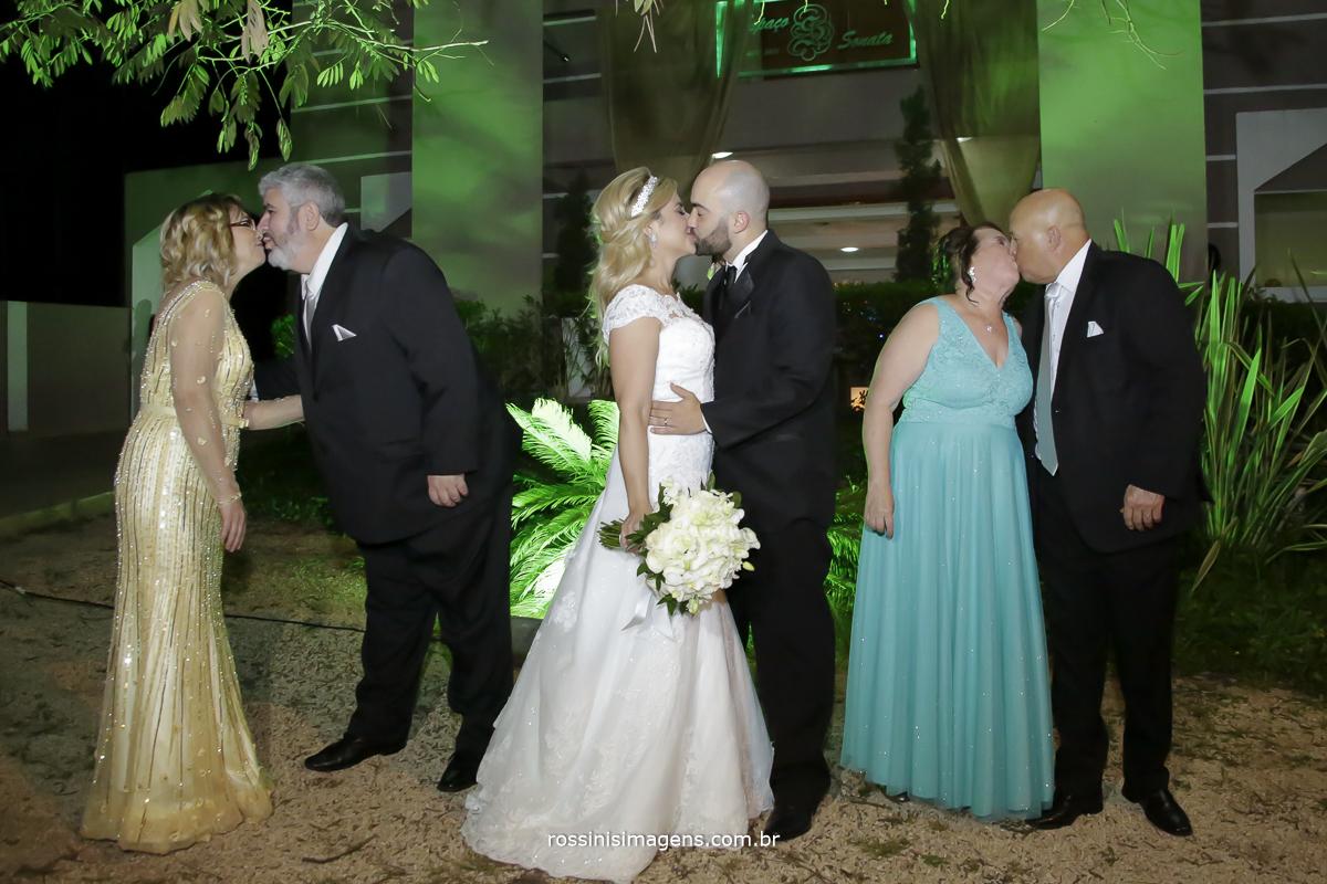 Fotografia diferente dos pais se beijando junto com os noivos um momento lindo