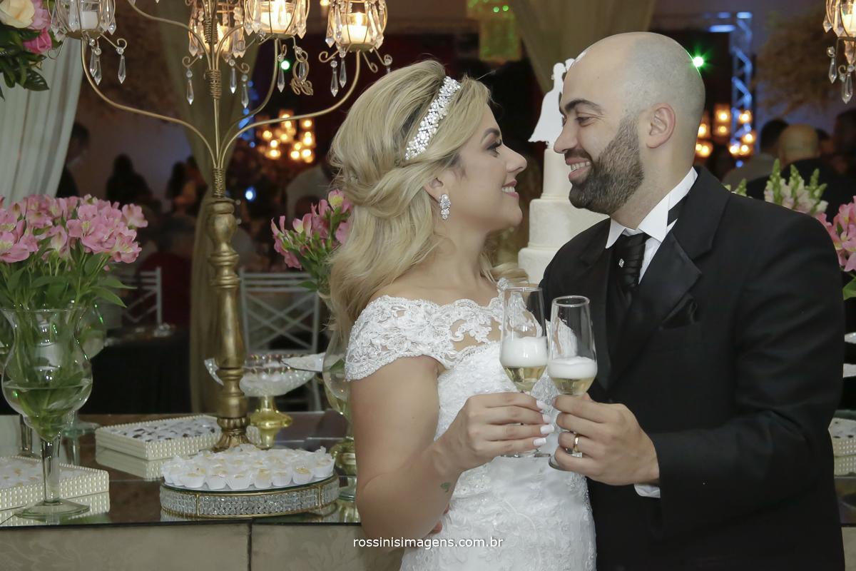 Brinde dos noivos para uma vida inteira juntos como uma familia maravilhosa que sao noivos na frente da mesa do bolo felizes