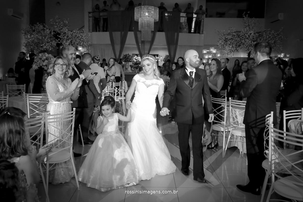 Fotografia preto e branco, pb da entrada dos noivos na recepção, para a festa uma linda festa de casamento muito amor com sua filha animando a vida do casal