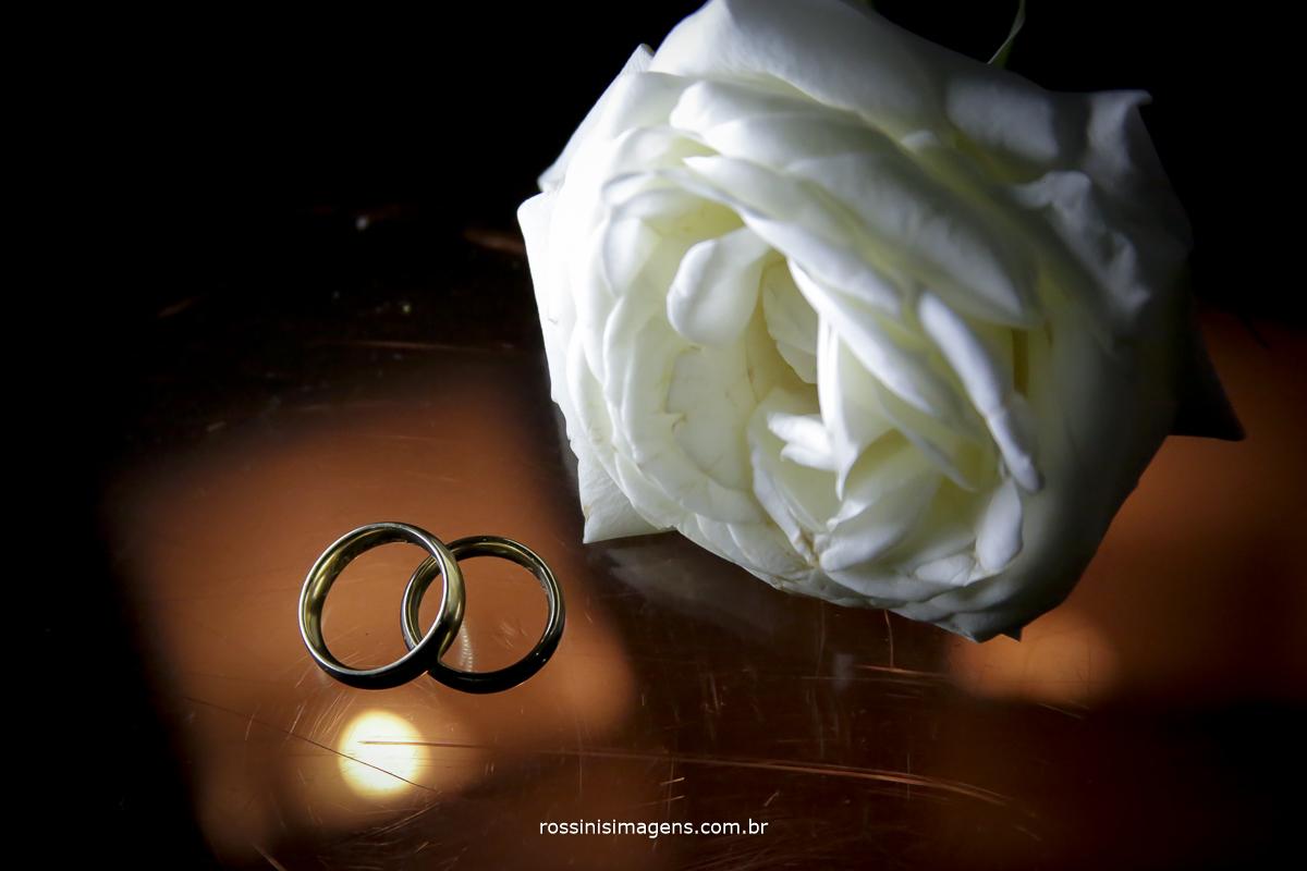 As aliança com uma rosa branca na composição registrando esse lindo e pequeno detalhe essa linda joia