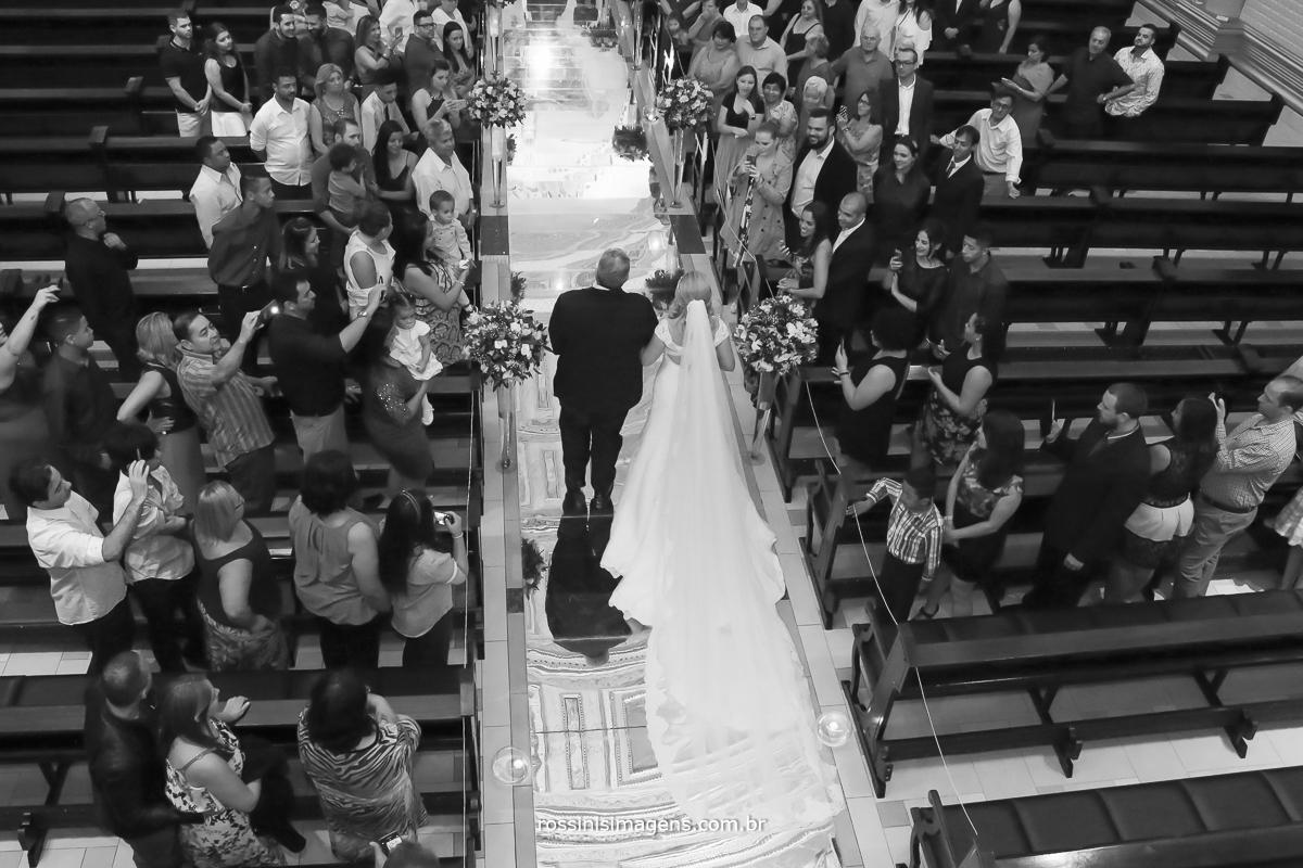 Entrada da noiva vista de cima da igreja conduzida pelo sei pai com uma linda passarela de espelhos