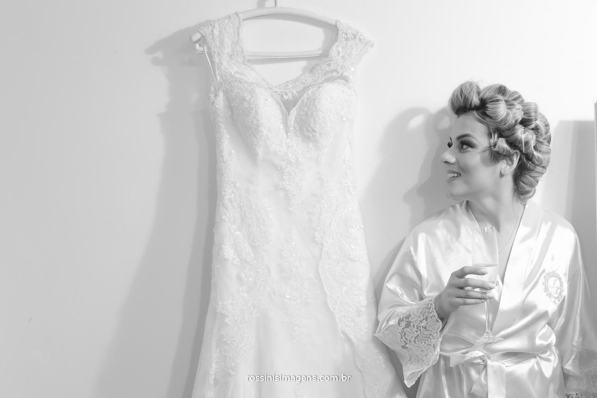 Noiva com taça de champanhe ao lado do vestido no dia da noiva