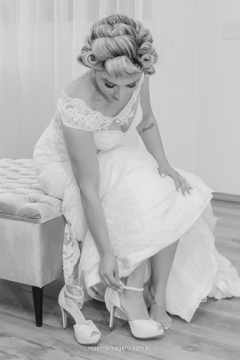 Noiva linda colocando o maravilhoso sapato para a cerimônia