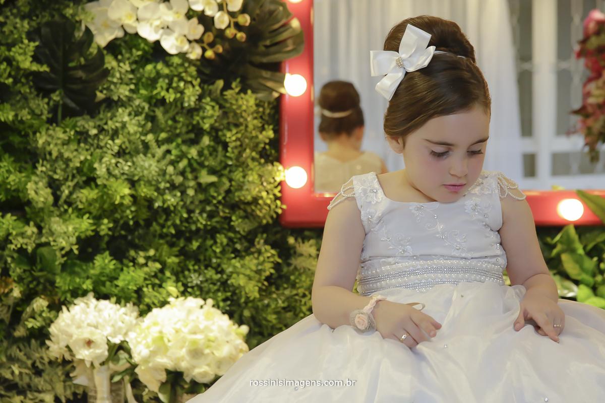 Filha da noiva de daminha olhando seu lindo vestido no making of da noiva kawana