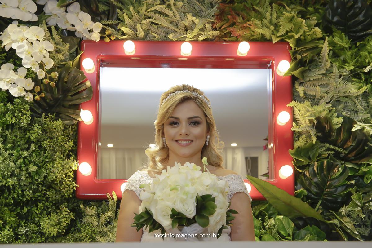 Noiva kawana no dia da noiva com o buquê na parede de muro ingles com flores