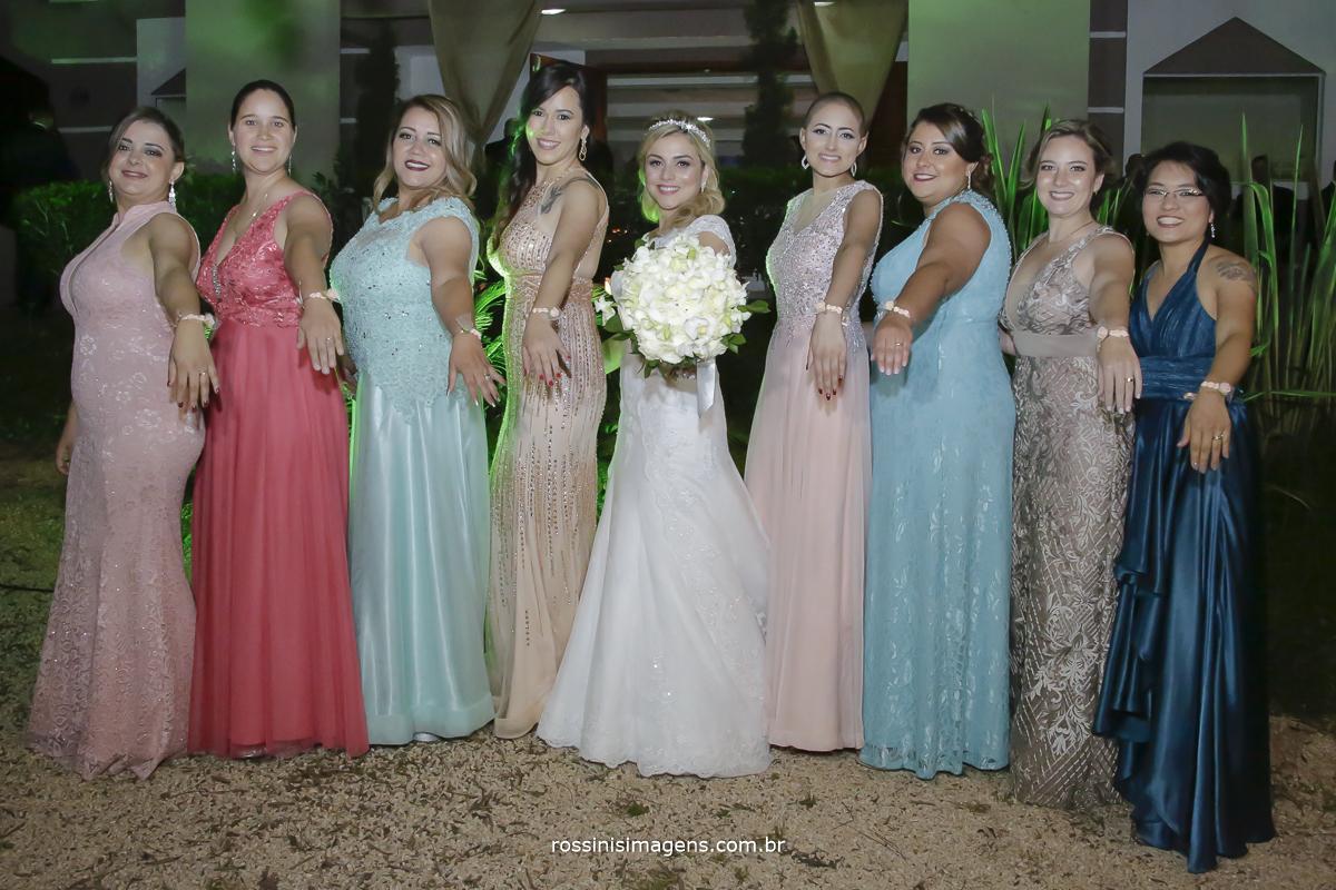 Fotografia da noiva com todas as madrinhas mostrando os vestidos os corsage e o lindo buquê
