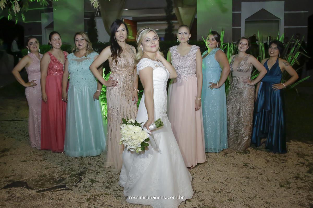 Madrinhas com a noiva divando mostrando os vestidos e a noiva arasando de vestido branco