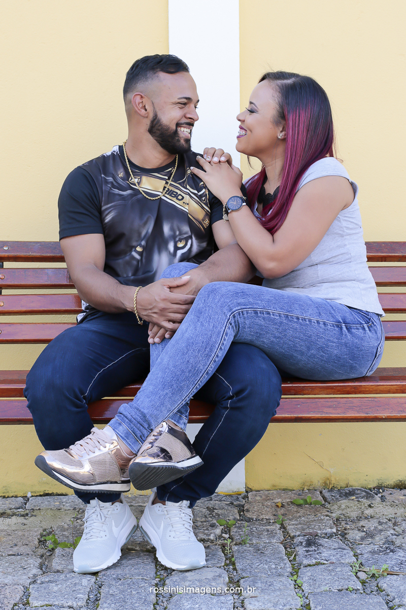 casal sentado em banco de madeira se olhando e sorrindo