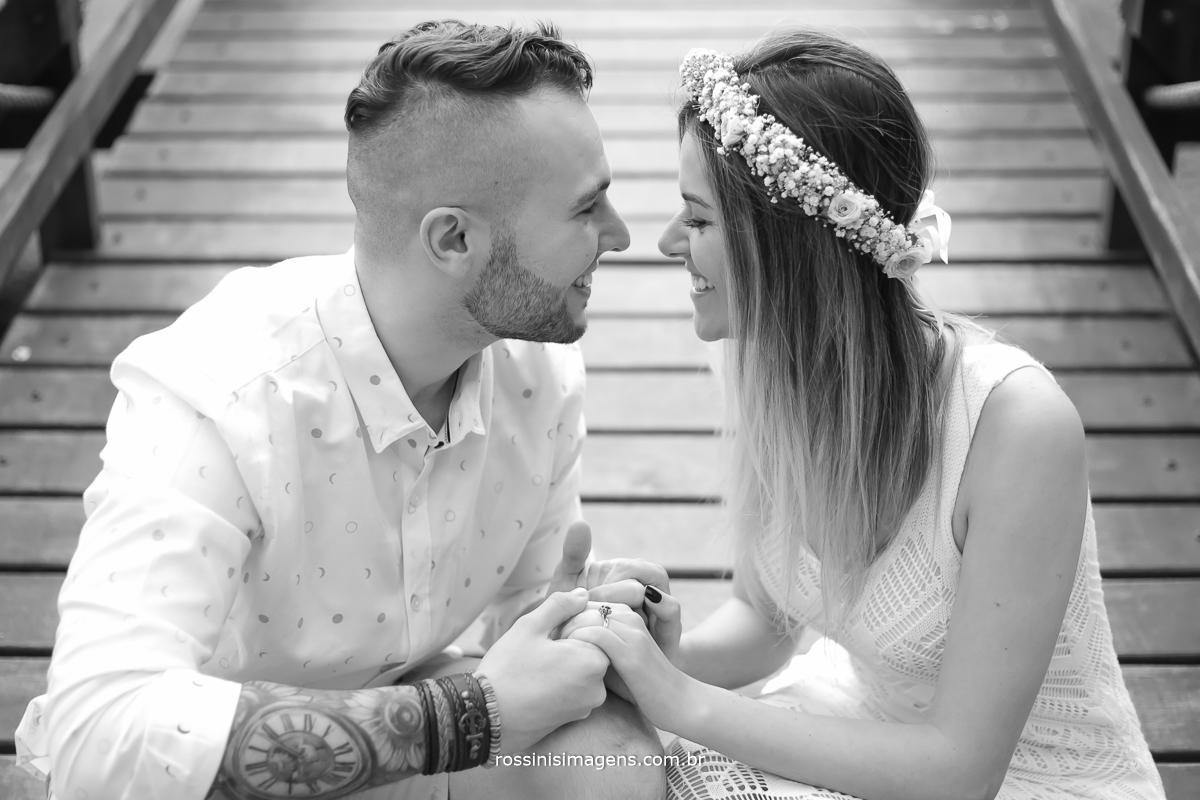 fotografia pb casal segurando as mãos e olhando um para o outro com sorriso no rosto