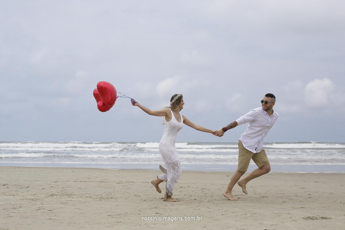 casal correndo na areia da praia, noivo puxando noiva com balão de coração