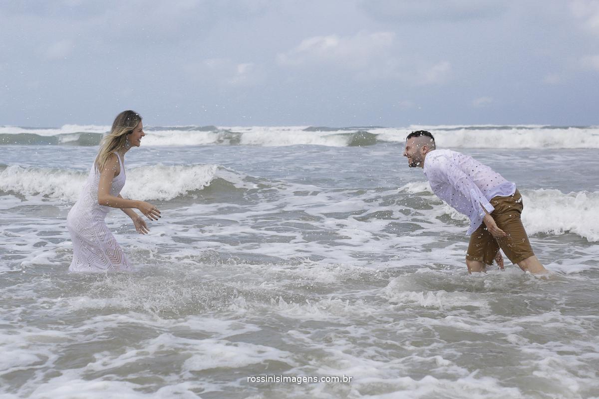 casal brincando no mar um jogando água no outro e felizes, noivos com roupas claras