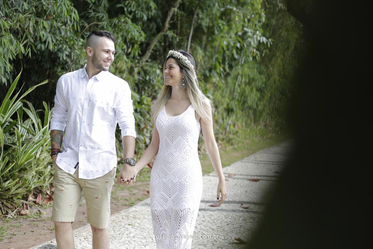 casal com roupas claras caminhando de mãos dadas no calçadão próximo a praia no ensaio fotográfico