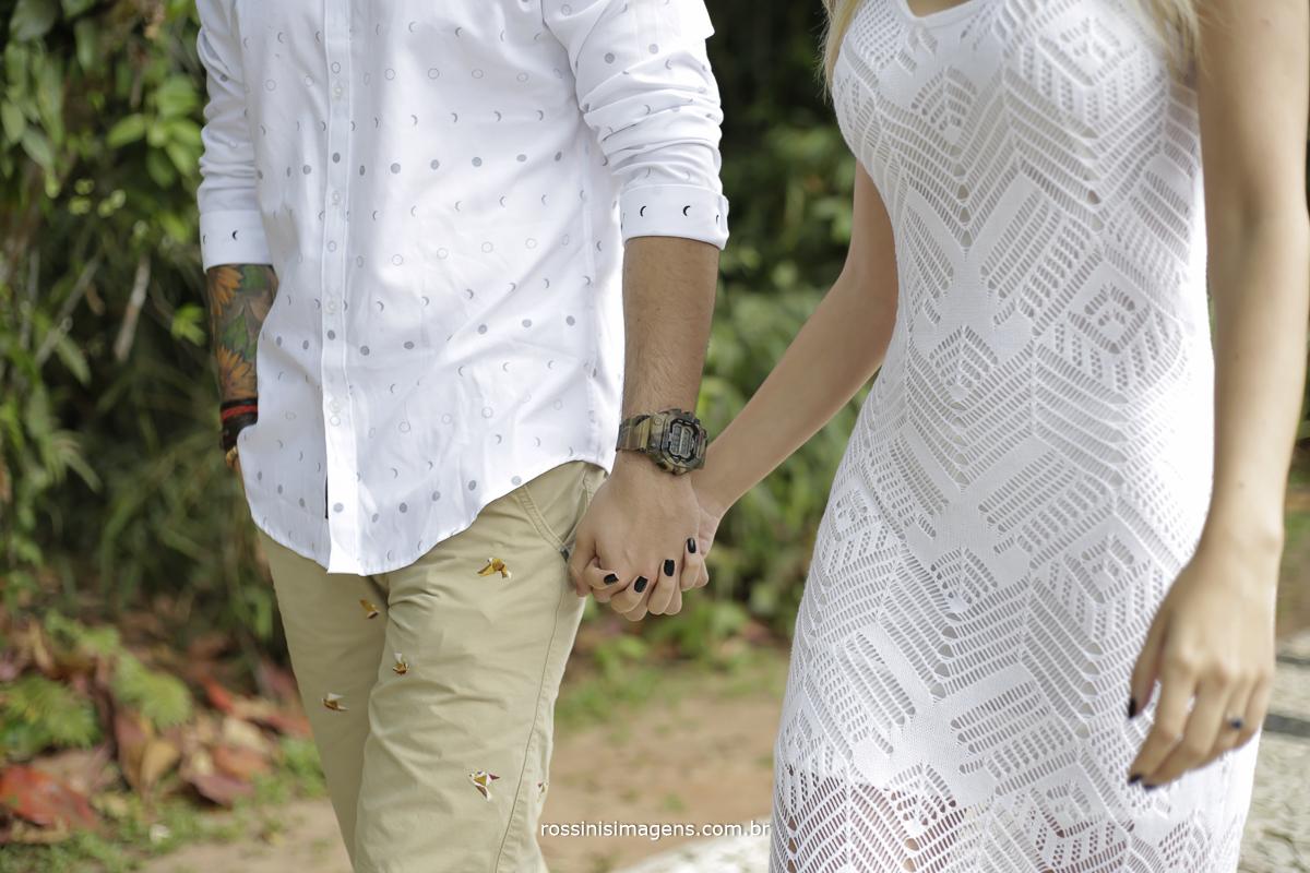 casal com roupa clara passeando na praia no ensaio para o casamento