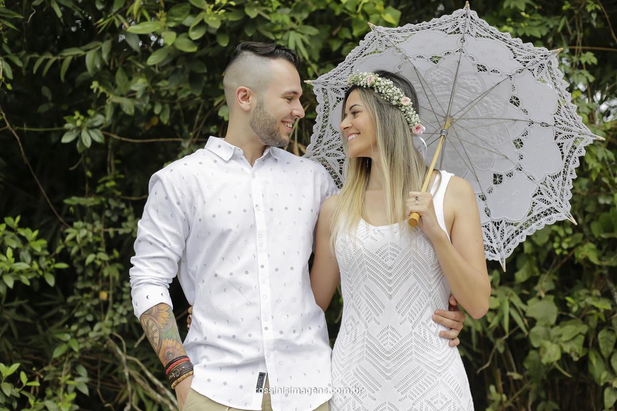 fotografia de ensaio pre casamento na praia com casal de camiseta branca e bermuda bege e noiva de vestido branco com sombrinha de renda branca