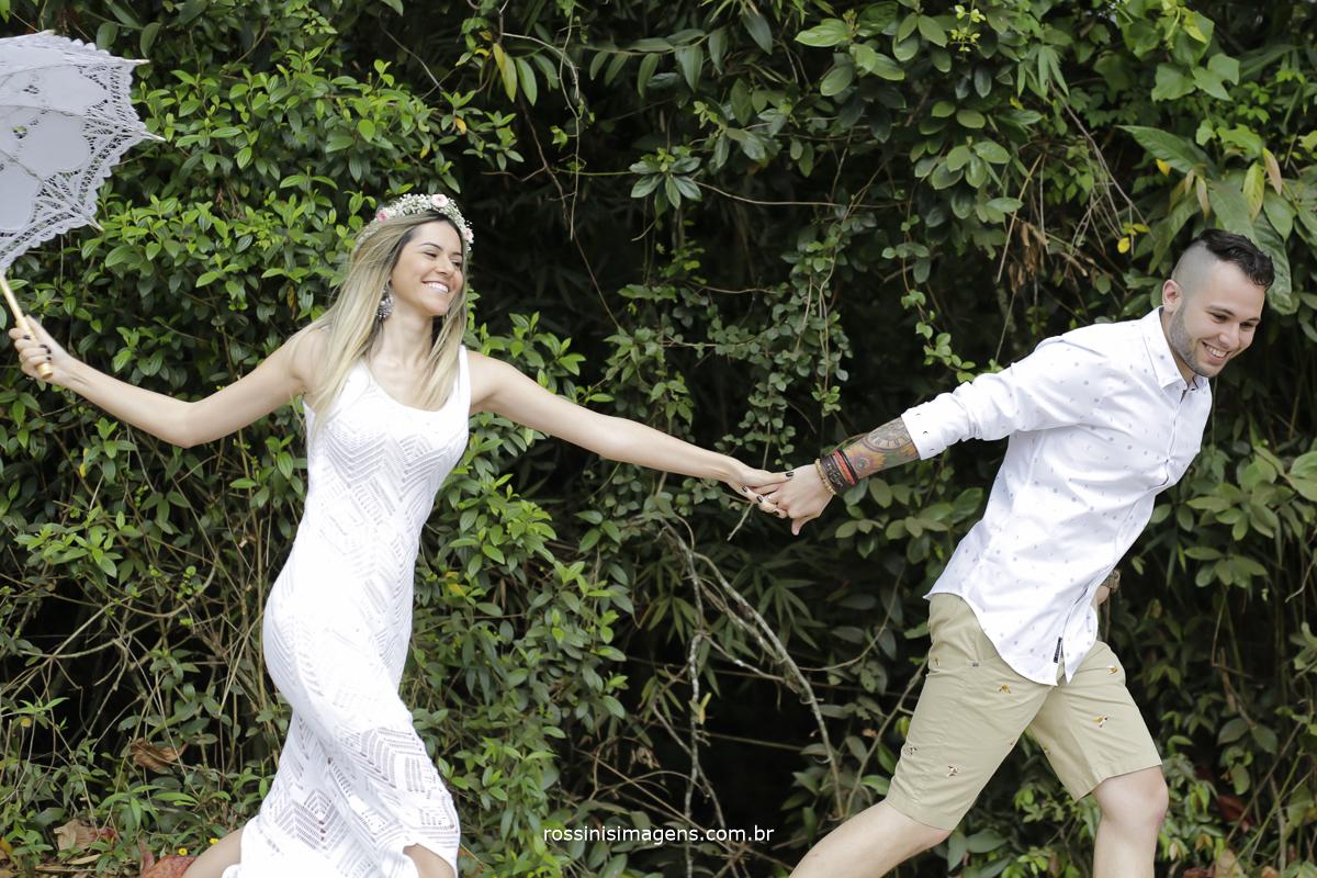 fotografia de ensaio com casal correndo feliz de fundo plantas e uma linda área verde