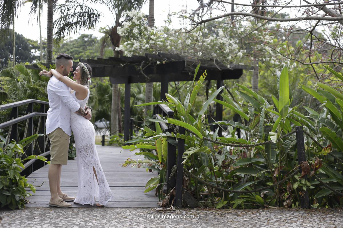 noivo e noiva abraçados em frente a ponte próximo a praia no ensaio pre casamento