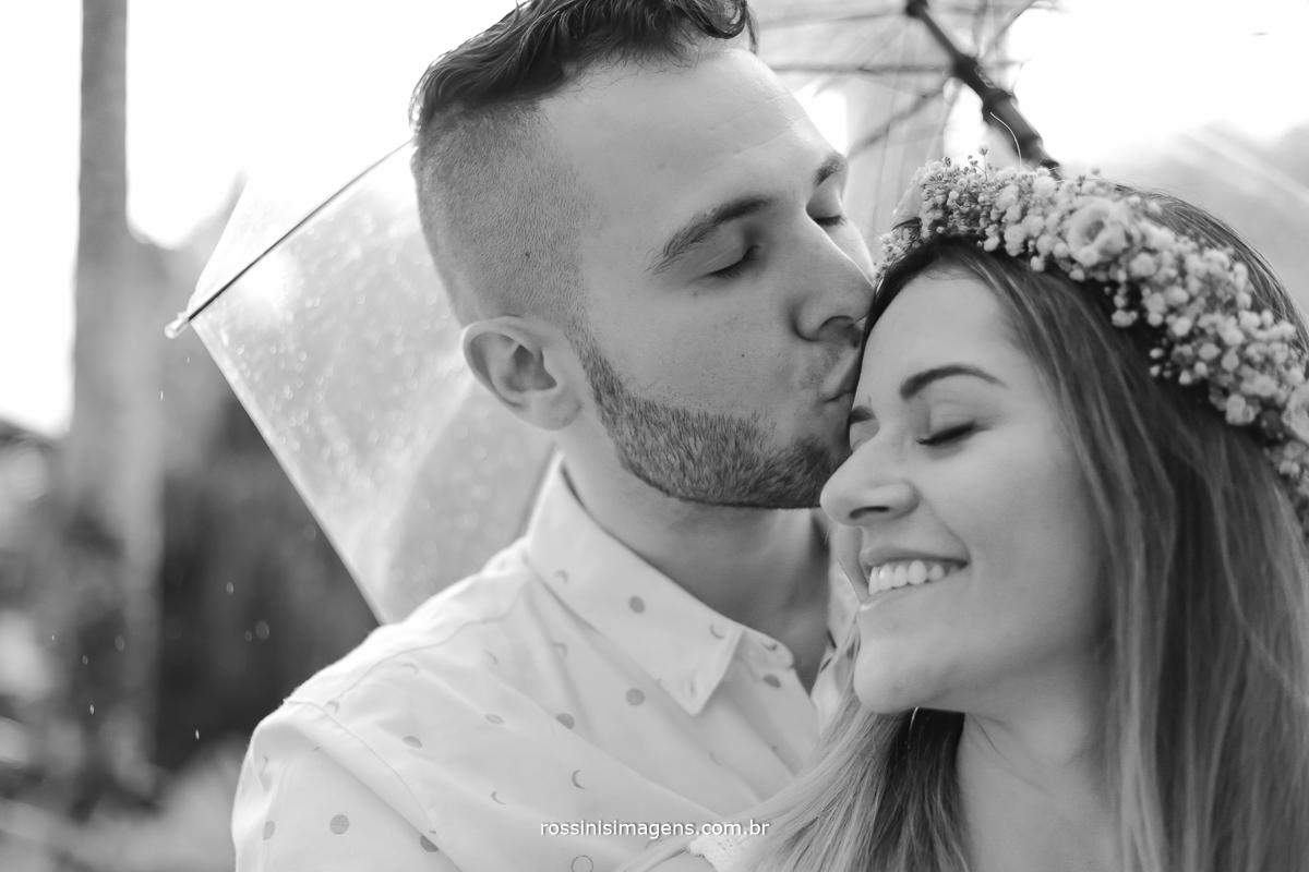 foto pb do noivo beijando a noiva no ensaio pre casamento na praia com chuva um ensaio lindo