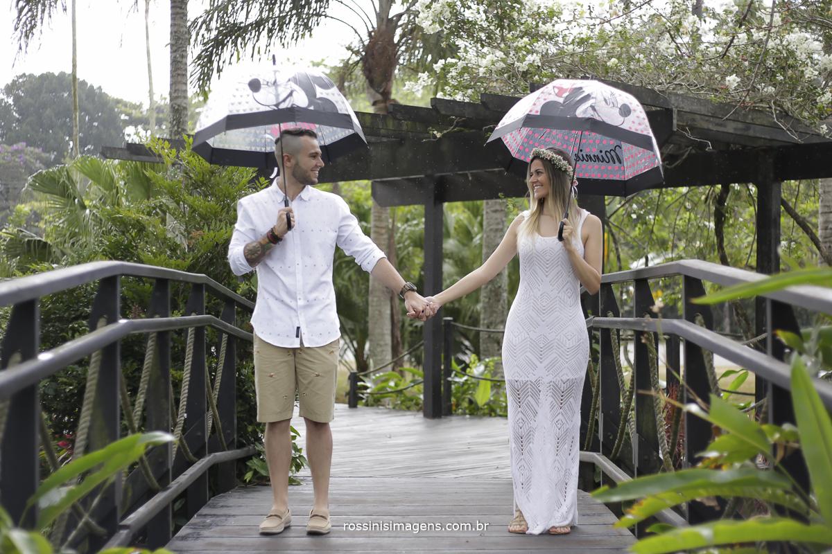 noivo de camiseta branca com bermuda caqui e sapato e sombrinha do michey e noiva com vestido branco sandália com  sombrinha da minnie no ensaio na praia