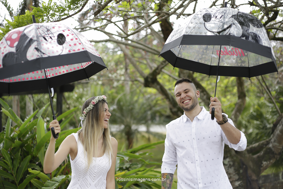 noiva camila com guarda-chuva da minnie rindo muito e noivo claiton com guarda-chuva do michey olhando pra foto