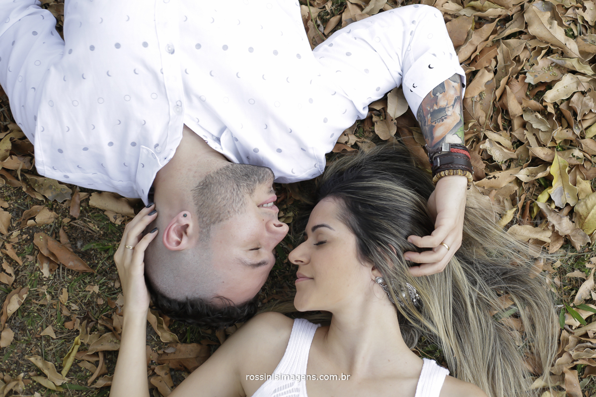 noivo de camiseta branca tatuagem no braço e pulseira fazendo carinho na noiva de vestido branco com os olhos fechados retribuindo o carinho deitados no chão com folhas secas caídas