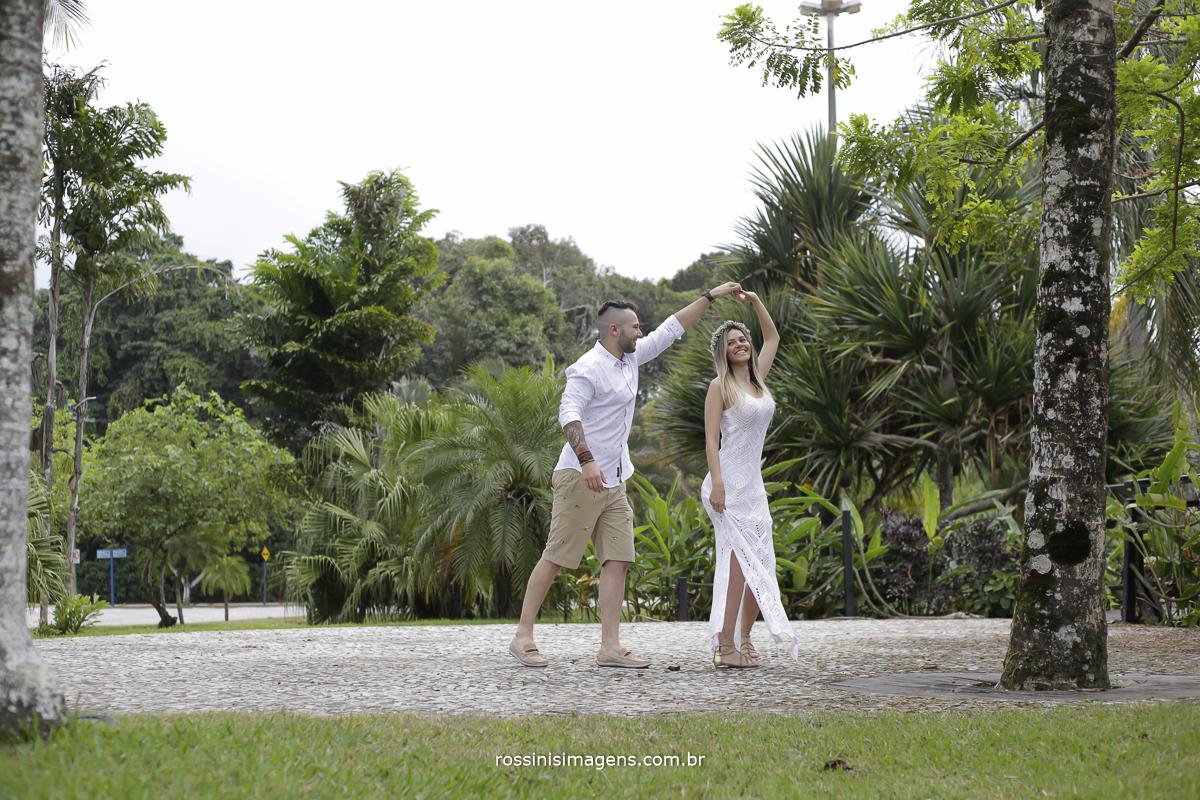 noivo dançando com noiva, fazendo a noiva girar em uma pequena área calçada em volta de arvores e plantas