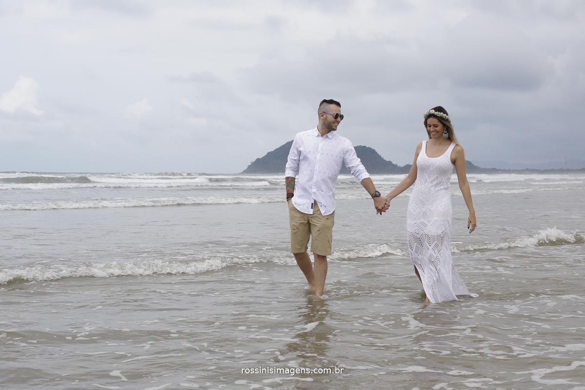 dia nublado no ensaio na praia com casal muito feliz caminhando na beira da praia, noivo com camiseta branca e bermuda caqui e de óculos escuros e noiva de vestido branco de renda com tiara de flores de mãos dadas