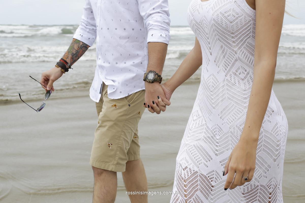 casal em ensaio na praia, homem segurando os óculos e de mãos dadas com mulher de vestido branco, lindo ensaio na praia