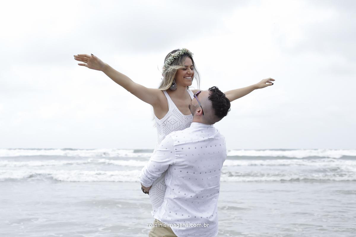 maravilhosos ensaio na praia de Riviera de São Lorenco, noivo com a noiva no colo de braços abertos felizes dentro do mar