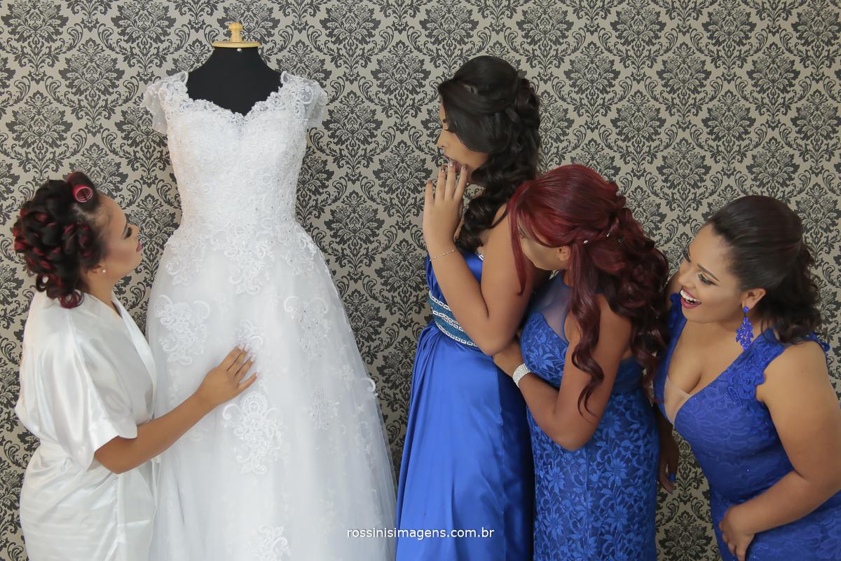 noiva Viviane olhando o vestido de noiva com as madrinhas admiradas com o vestido e todas as madrinhas de vestido azul