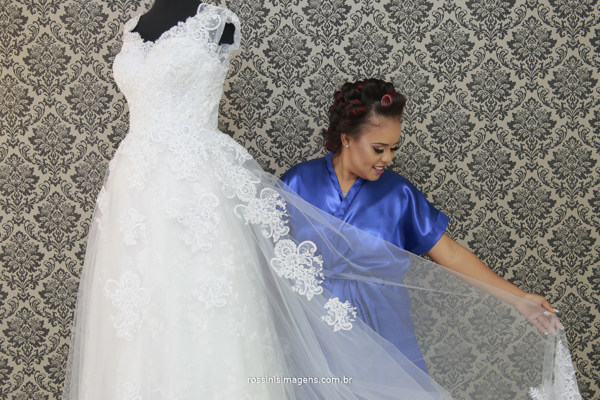 noiva com robe azul mostrando o vestido branco do casamento