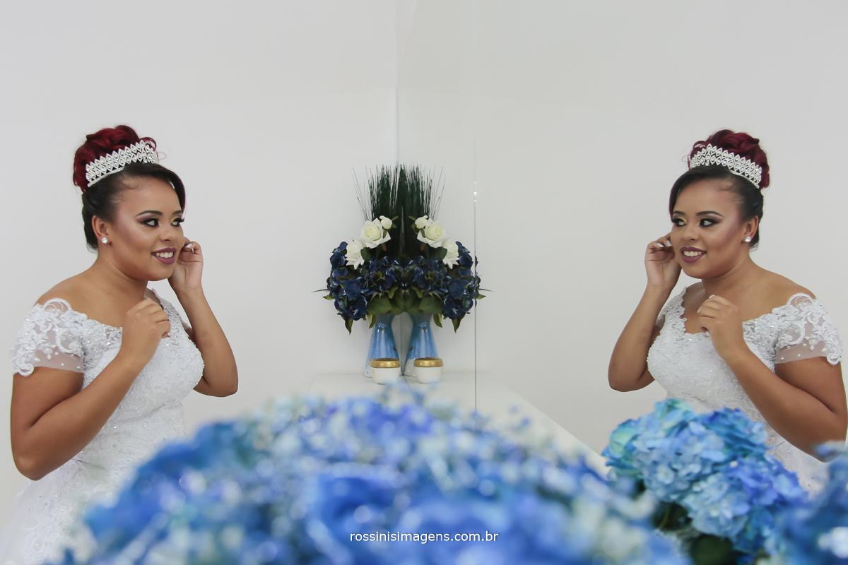 foto do making of da noiva, colocando o brinco em frente ao espelho, e o lindo buquê azul