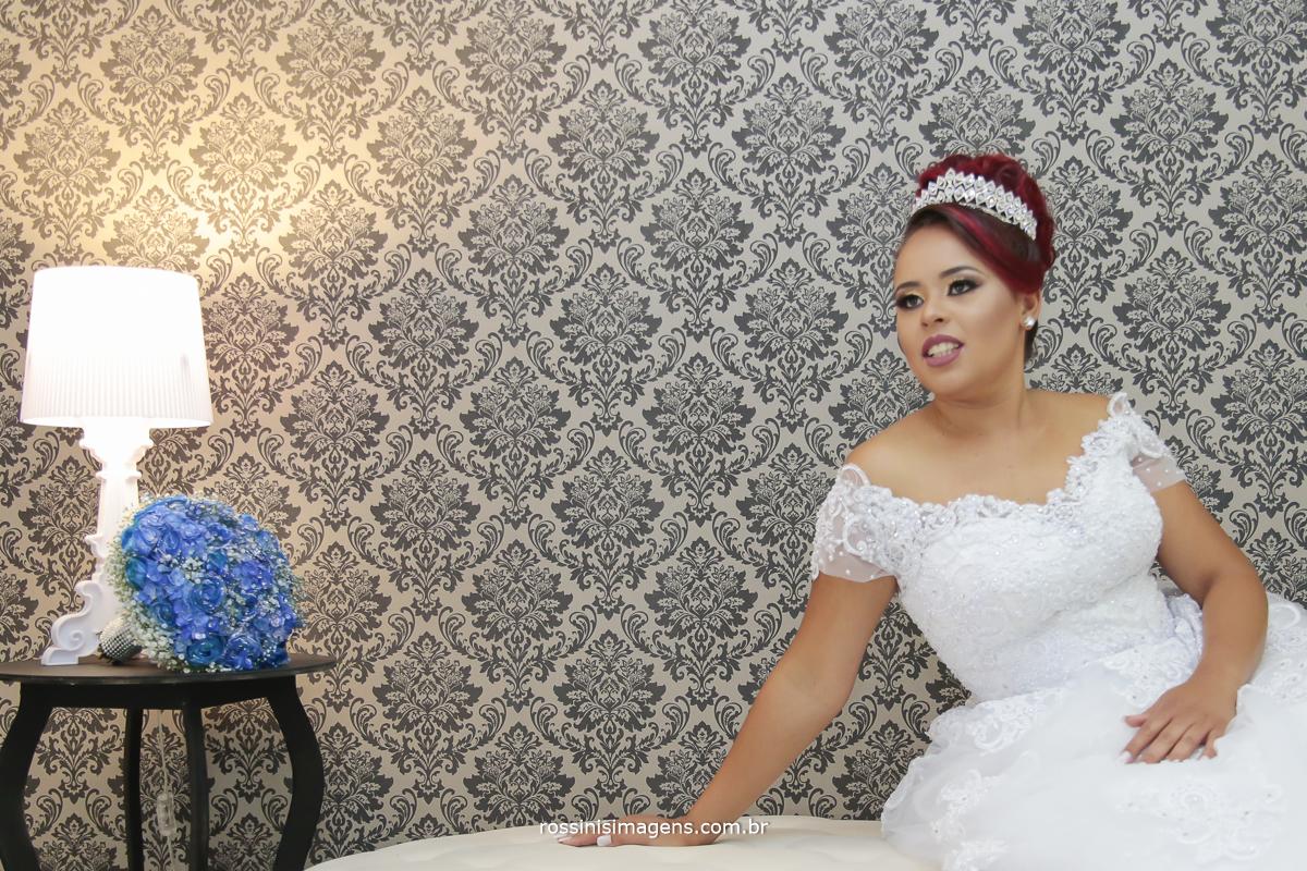 noiva feliz, sentada no banco no dia da noiva com o buquê azul de fundo