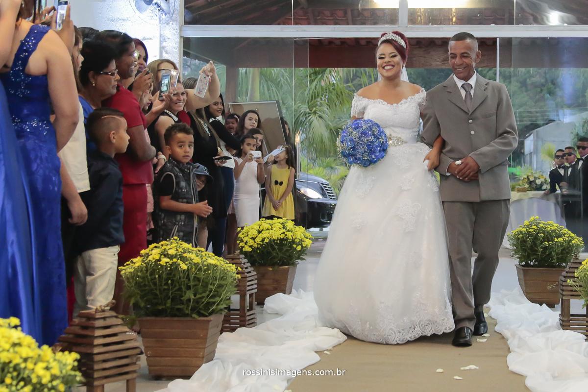 entrada da noiva de vestido branco  e buquê azul com seu pai com terno cinza