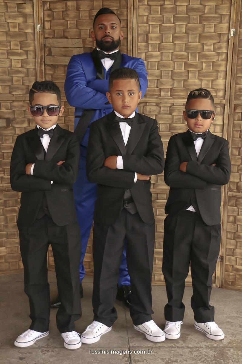noivo de terno azul com os pajens, crianças com terno preto de óculos escuros, entrada da aliança