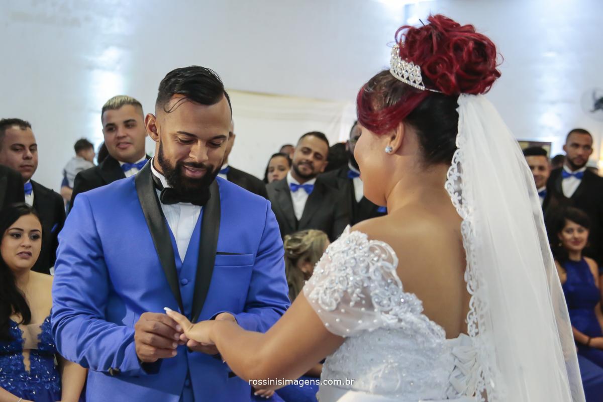 foto do noivo trocando as alianças de casamento com a noiva, casamento lindo em azul