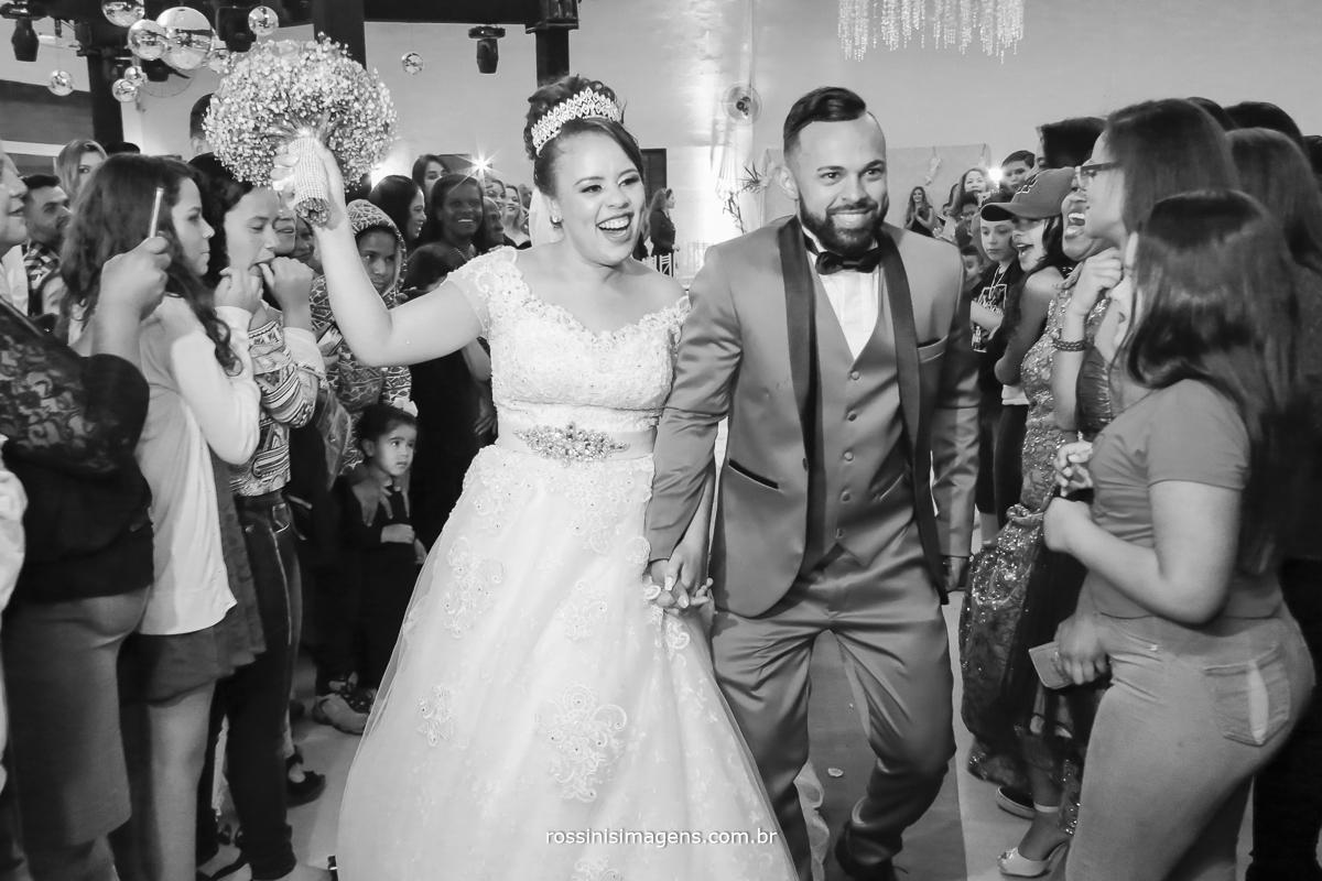 saída dos noivos muito animada, vibrante, do casamento em poá