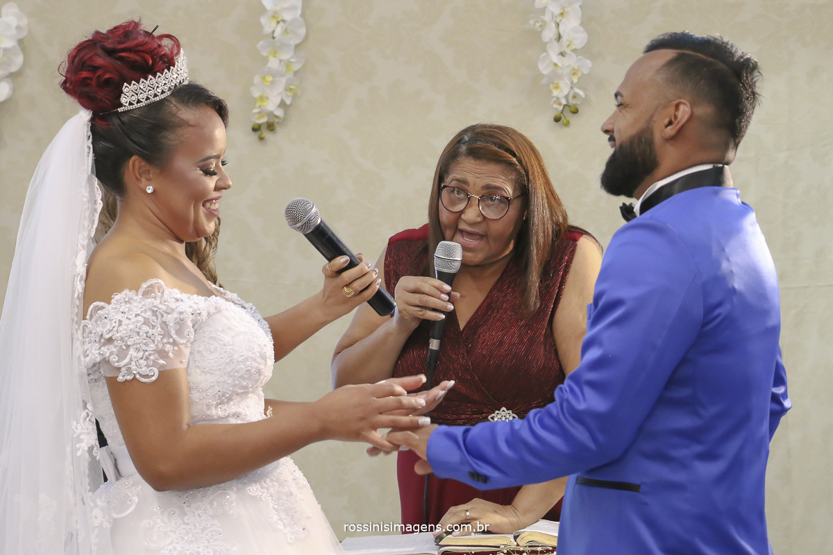 fotografia noiva e noivo trocando as alianças,