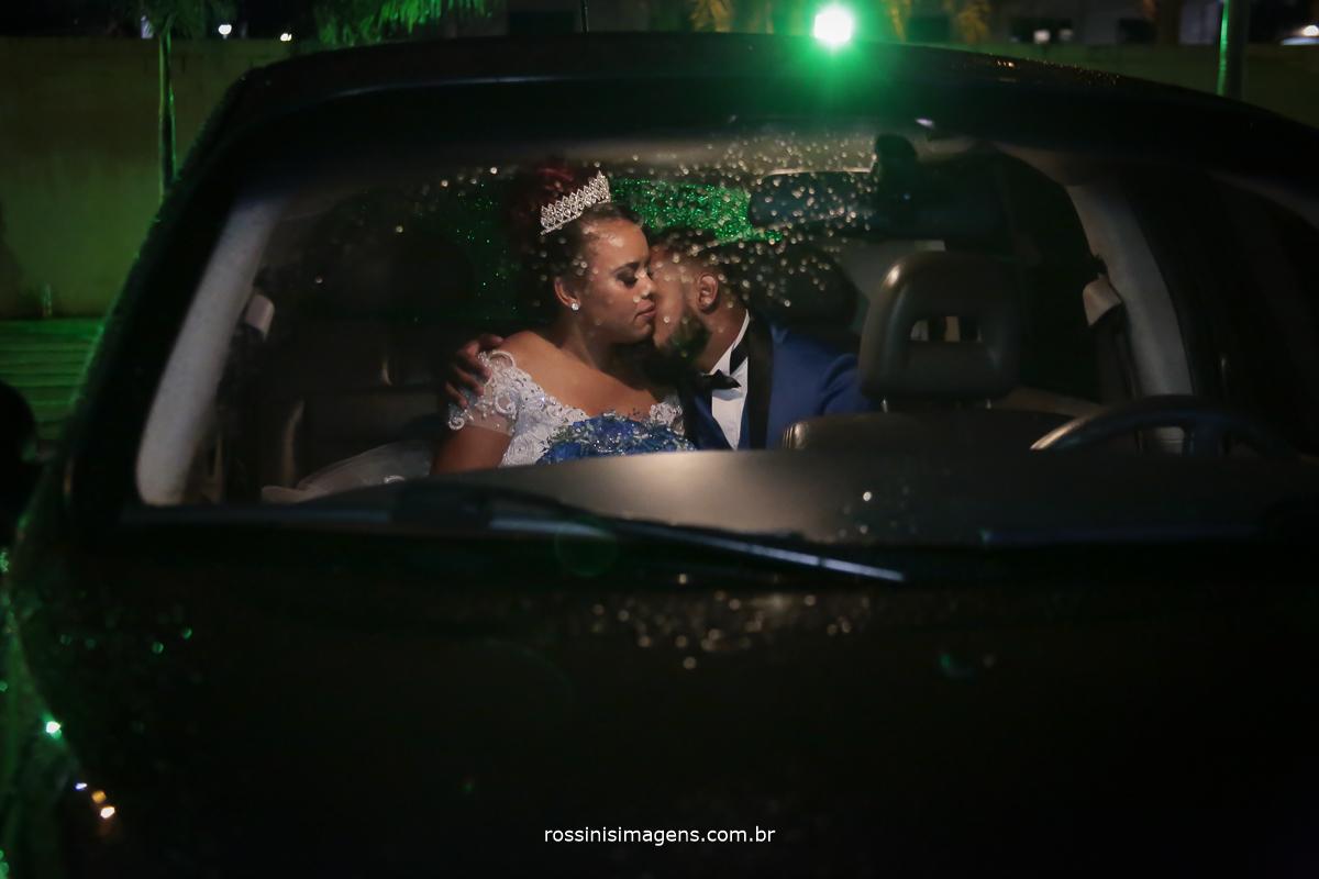 fotografia do casal dentro do carro se beijando durante a chuva