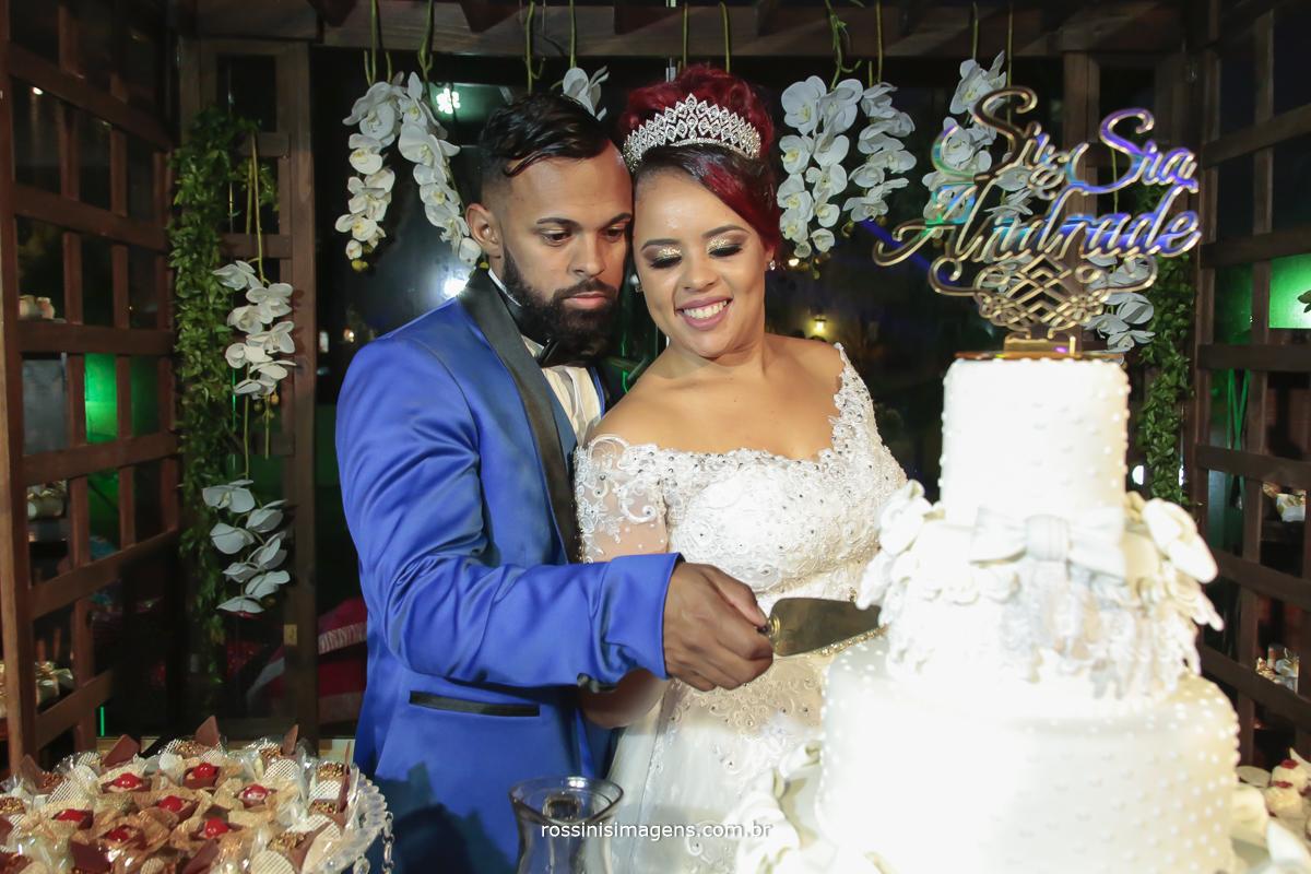 fotografia de casamento com os noivos fazendo o corte do bolo muito animado e felizes mesa do bolo linda