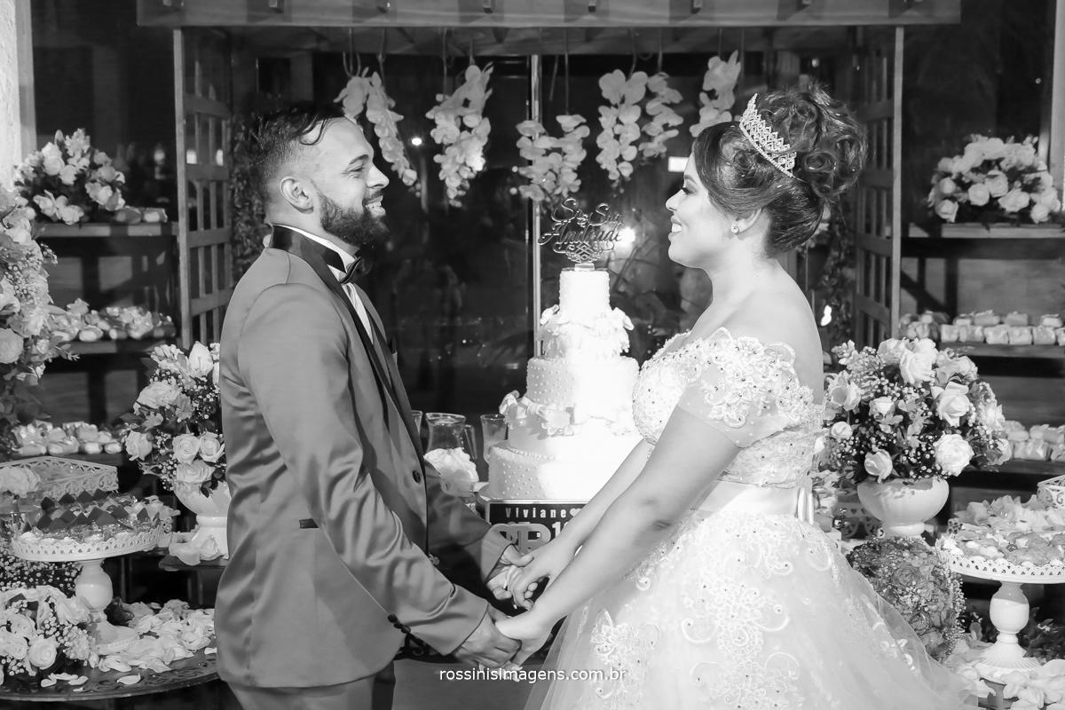fotografia de casamento casal na frente da mesa do bolo com um lindo olhar de amor de conquista, realização do sonho do casamento