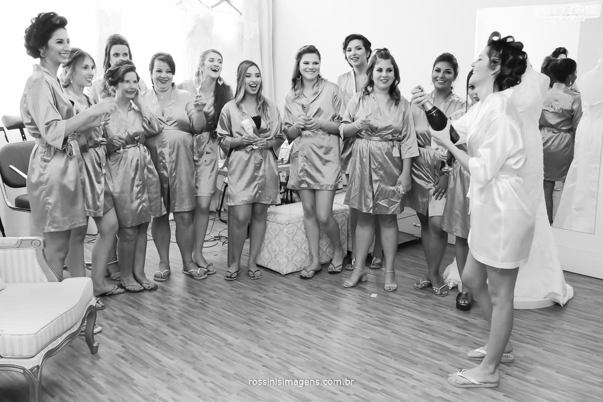 fotografia noiva com robe personalizado branco, abrindo garrafa de champanhe com as madrinhas de robe com taça na mão, muito alegre e sorrindo