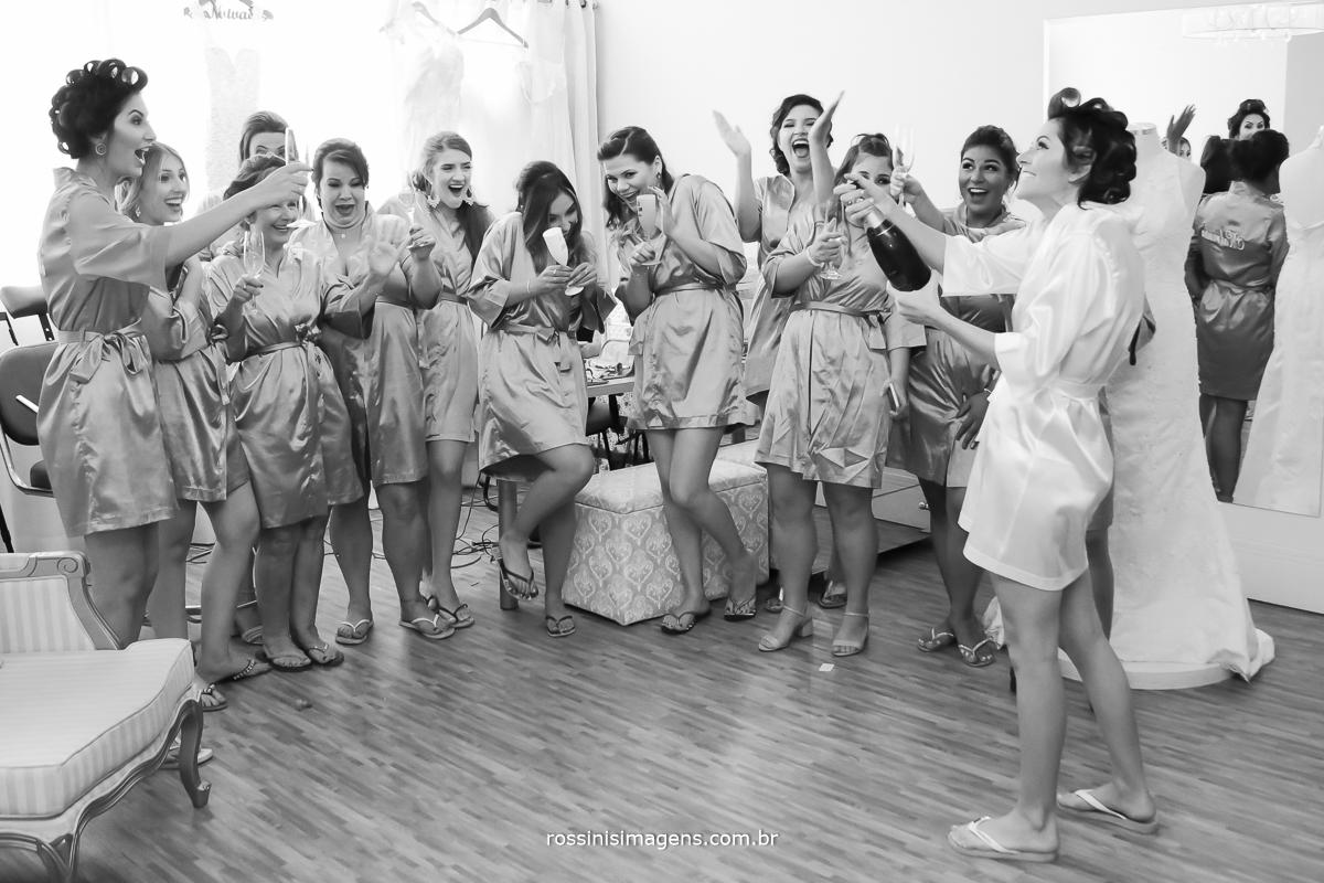 noiva estourando a champanhe feliz e as madrinhas tomaram um susto e estão feliz e sorrindo muito uma alegria sem tamanho