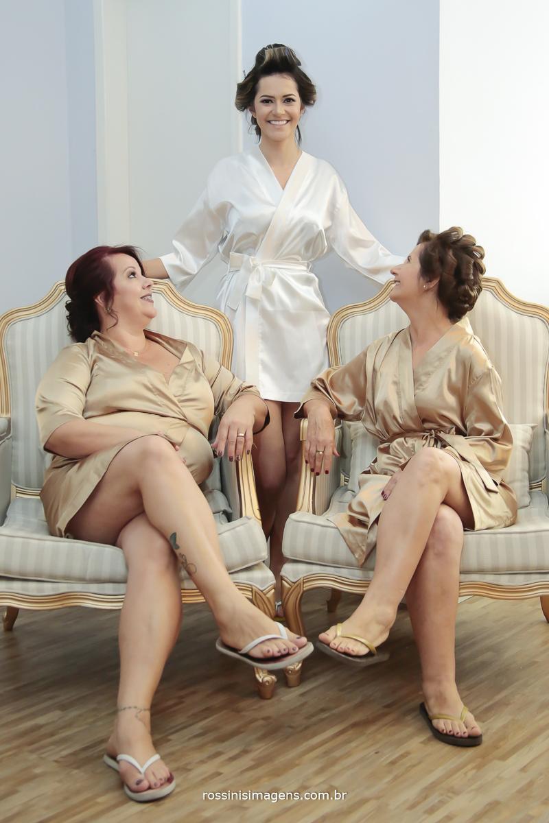 foto da noiva de bobs em pé com a mãe e a sogra,sentadas na cadeira muito elegante no making of, dia da noiva, e os robe personalizados