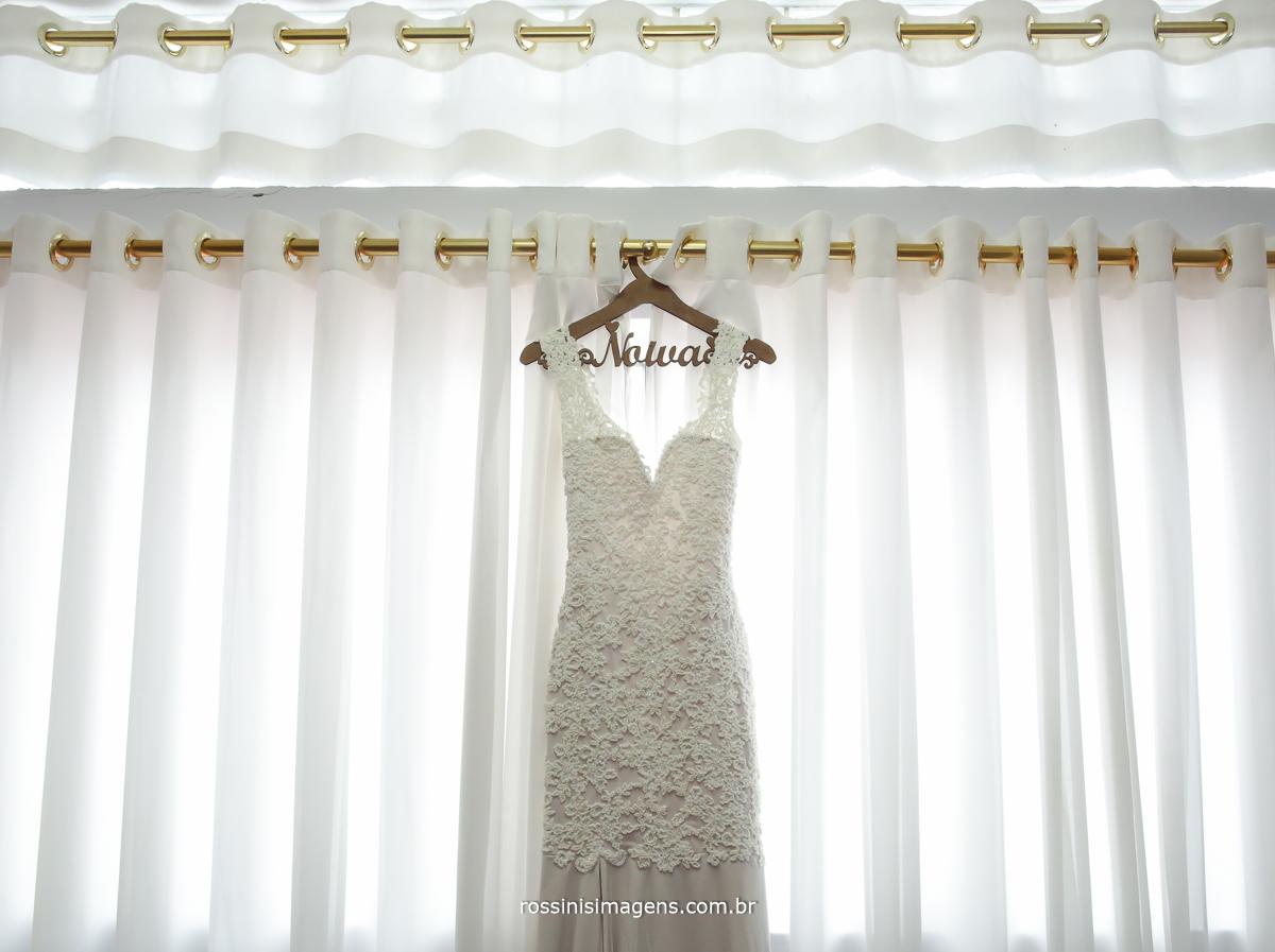 fotografia do vestido da noiva camila no cabide personalizado pendurado na frente a janela, vestido feito sob encomenda pelo Ateliê Dalva Machado, exclusivo vestido de noiva, branco, lindo