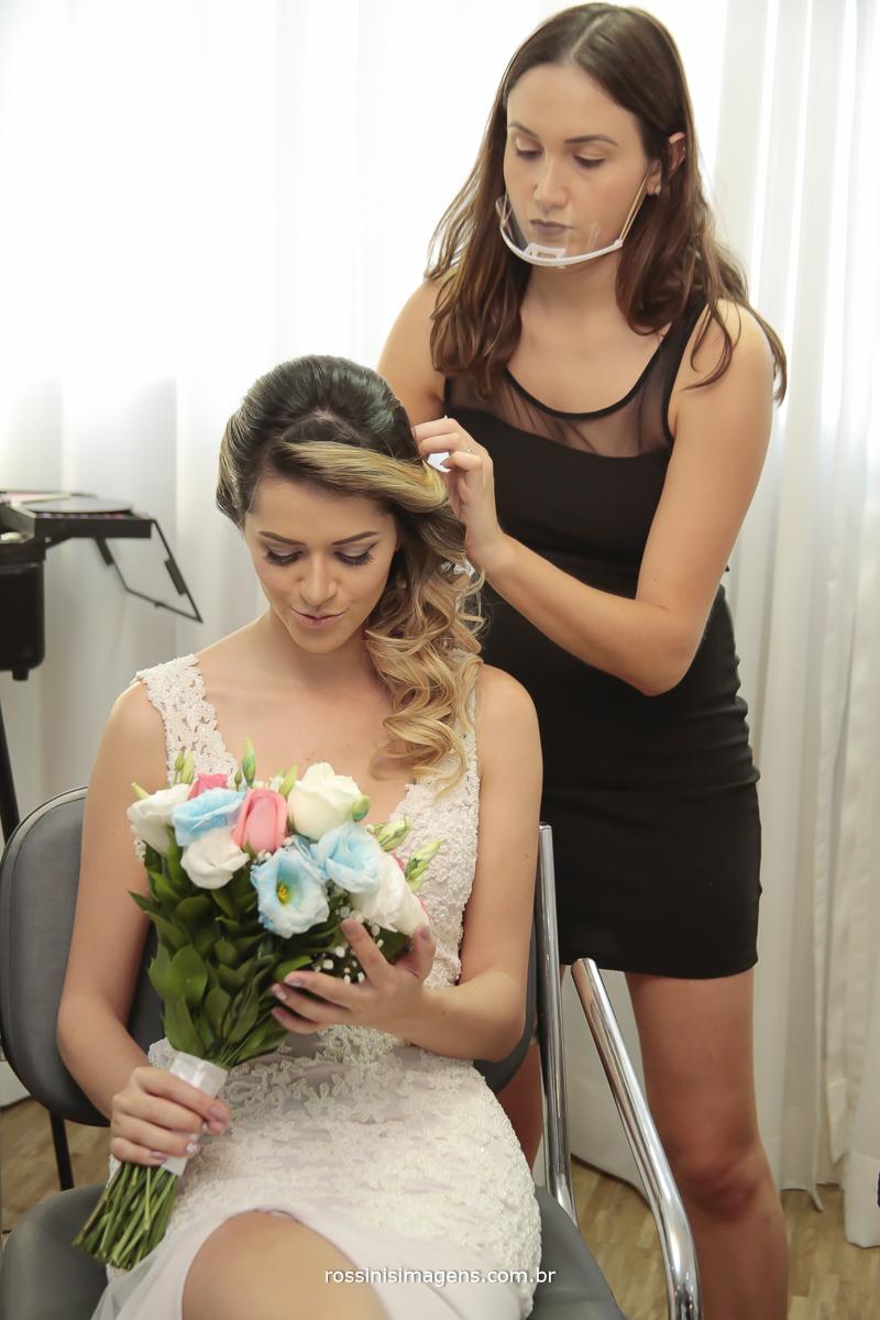 bruna torres na preparação da noiva camila executando o penteado e maquiagem para o casamento, noiva sentada com o vestido com o maravilhoso buquê em mãos