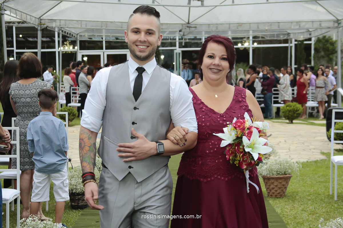 imagem da linda entrada do noivo no tapete ao ar livre com sua mãe de vestido vermelho e um maravilhoso buquê de lírios e seu filho o noivo de camisa branca gravata preta, colete e calça cinza, casamento ao ar livre de dia