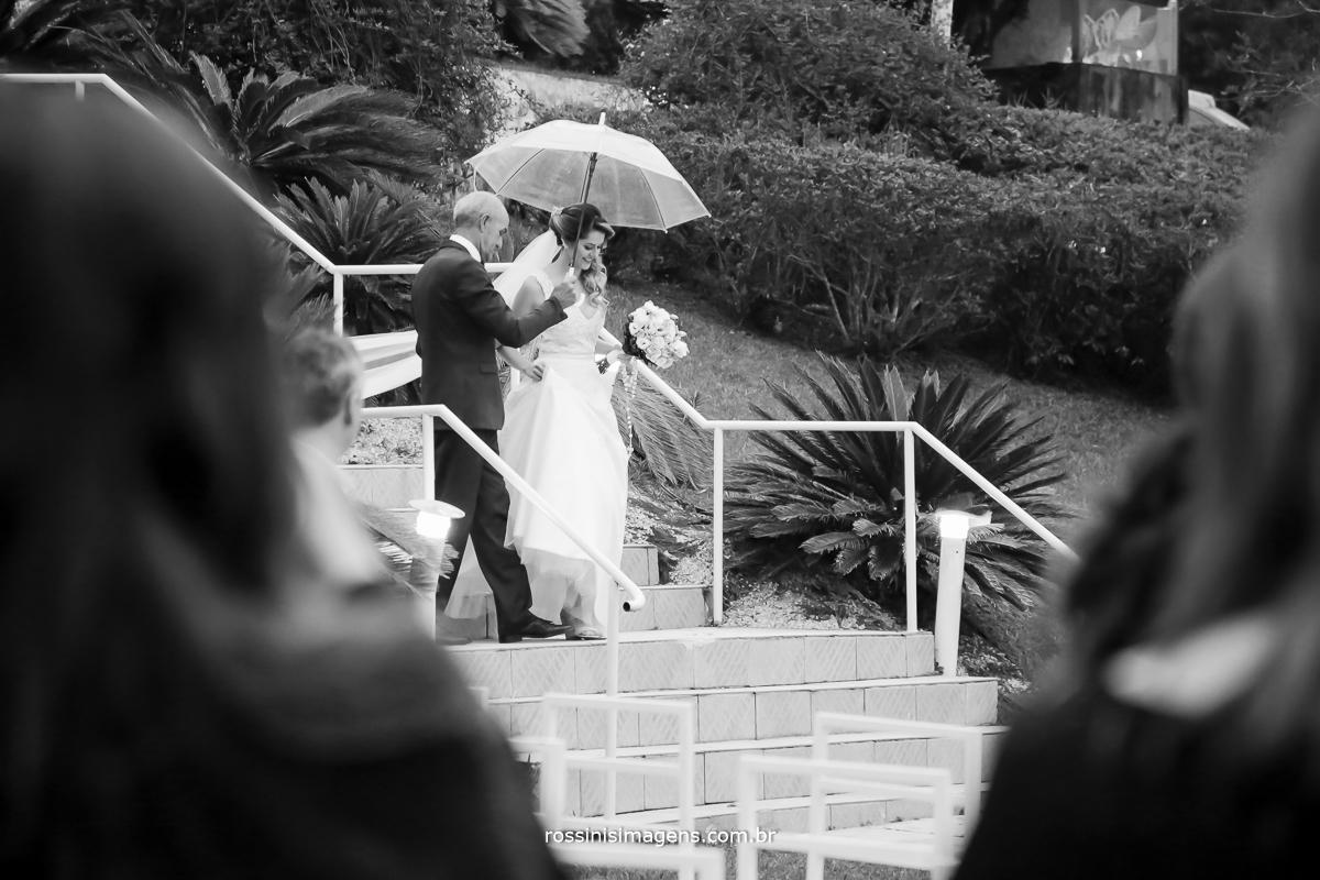 fotografia de casamento pai descendo com a noiva pelas escadas com o guarda chuva, para a entrada da noiva na cerimonia de casamento